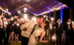 Groom kissing bride sparkler exit
